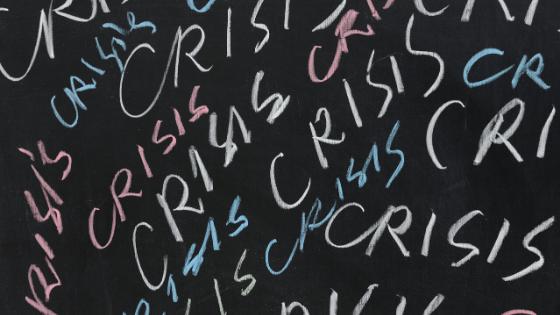 Crisis written on chalkboard in multiple colors